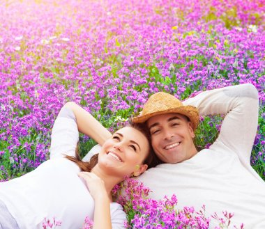 Beautiful happy couple lying down on purple lavender field, having fun on floral glade, summer nature, love concept stock vector