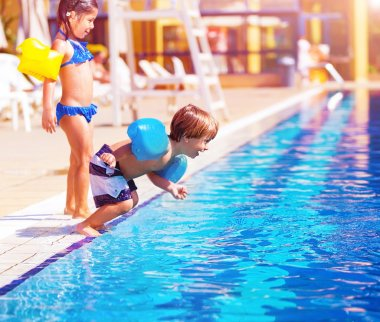 Cute little boy jumping into the pool, brother and sister having fun in poolside, water amusement, luxury beach resort, summer vacation, happy childhood stock vector
