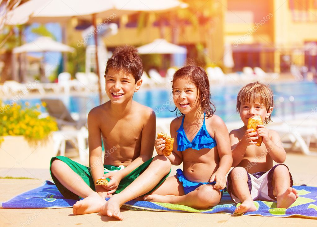 Three kids sitting down and eating croissant near pool, picnic outdoors, beach resort, summer vacation, happy childhood concept