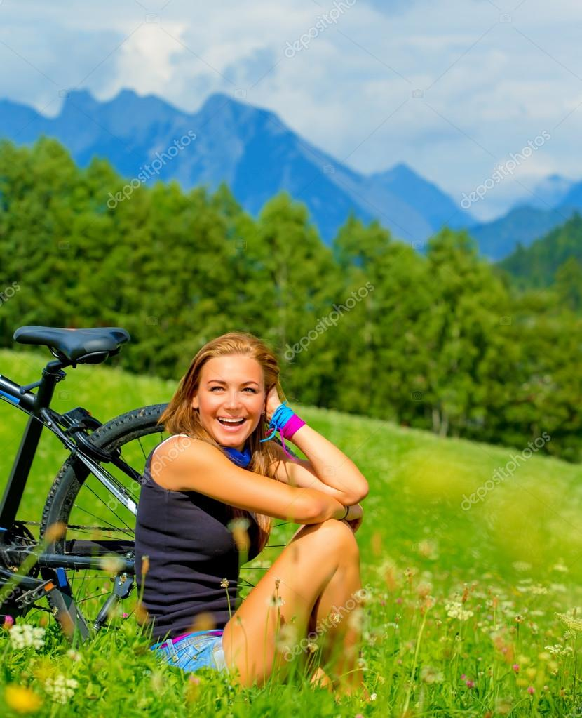 Cheerful female resting on green field after riding on bicycle, Alps mountains background, biking traveling along Austria, summer vacation concep stock vector