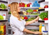 šťastné ženy hledat něco v lednici