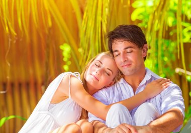 Portrait of happy couple sitting and hugging outdoors with eyes closed in pleasure, spending summer holidays on paradise beach stock vector