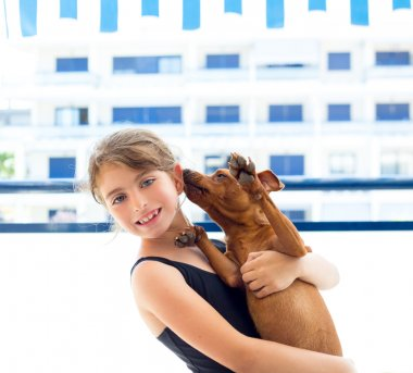 Brunette kid girl in swimsuit playing with dog