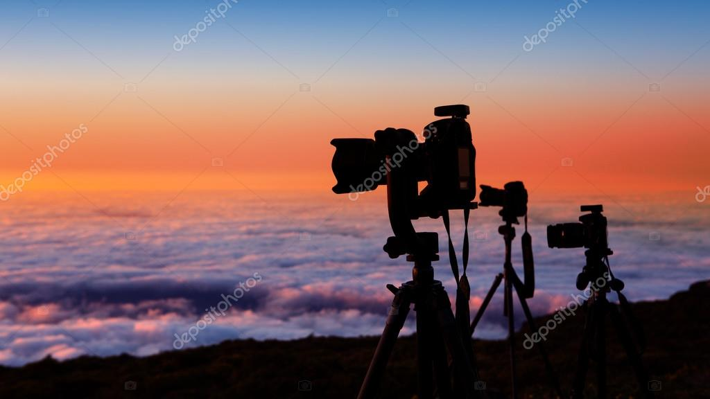 camera tripods photographer sunset sea of clouds