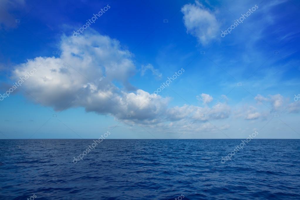 cumulus clouds in blue sky over water horizon