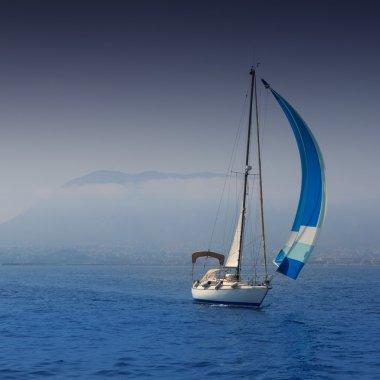 Blue sea with sailboat sailing in a foggy coast