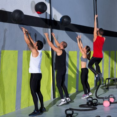 Crossfit workout group with wall balls and rope
