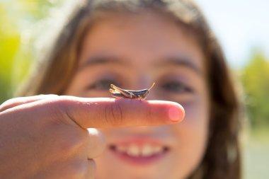 kid hand holding grasshopper bug macro