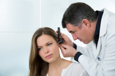 Doctor ENT checking ear with otoscope to woman patient