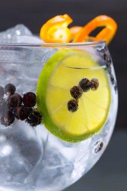 Gin tonic cocktail macro closeup with juniper berries