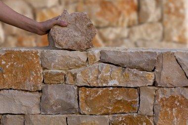 Mason hands working on masonry stone wall