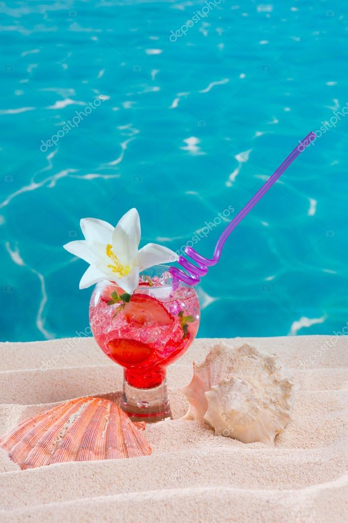 tropical red cocktail on caribbean sand flower and seashell