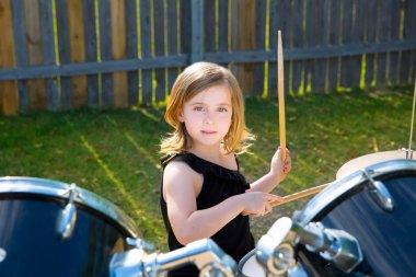 Drummer blond kid girl playing drums in tha backyard