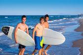 Fiúk szörfösök csoport jön ki a strandtól