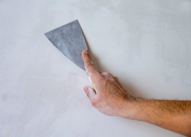 Plastering wall with plaste and plaster spatula trowel