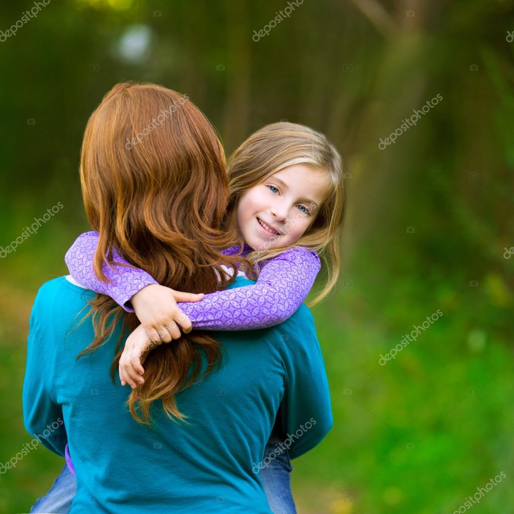 Mum holding daughter kid girl in her arms rear view smiling