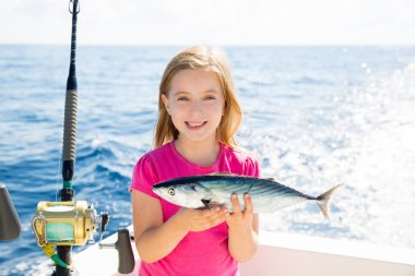 Blond kid girl fishing tuna bonito sarda fish happy catch