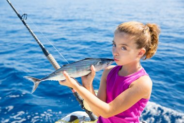 kid girl fishing tuna bonito sarda kissing fish for release