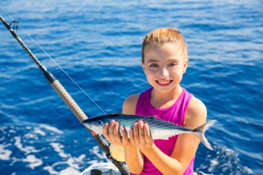 kid girl fishing tuna bonito sarda fish happy with catch