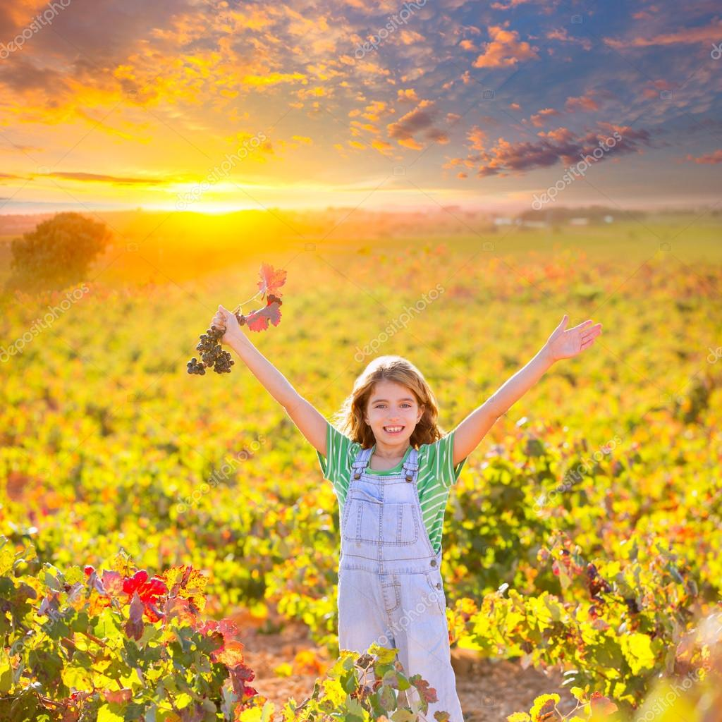 Kid girl in happy autumn vineyard field open arms red grapes bun
