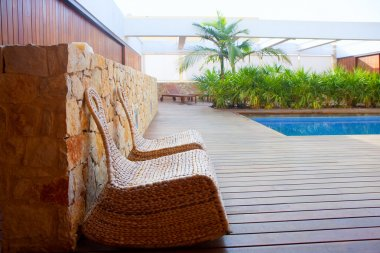 Teak wood house outdoor with swing chairs and pool