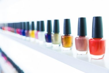 colorful nail polish colors in a row at nails saloon on white