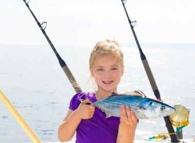 Blond girl fishing bonito Sarda tuna trolling in sea