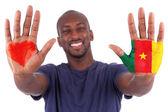Fotografia mani di uomo africano con una bandiera dipinta di cuore e Camerun, amo