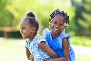 Outdoor  portrait of a cute young black sisters - African people