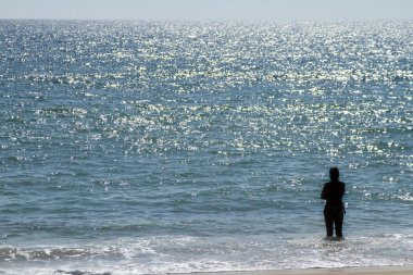 Lonely figure stares at the ocean