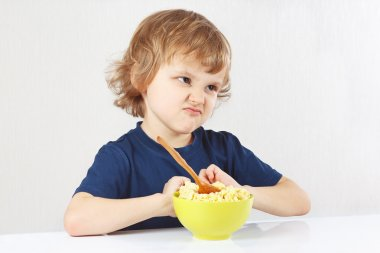 Little cute blonde boy refuses to eat porridge