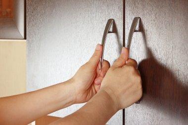 Women's hands closed the cupboard doors, dark wood