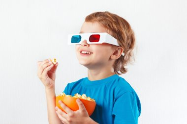 Young smiling boy in stereo glasses eating popcorn