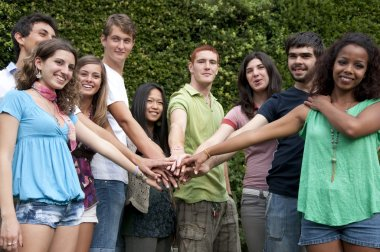 Group of young students with hands on stack