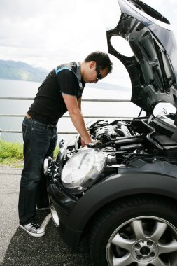 A young man fixing his car up the hills