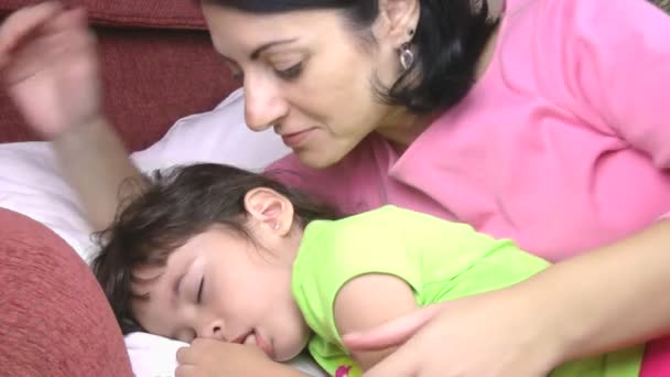 Close up of mother watching her little daughter sleeping, then kiss her.