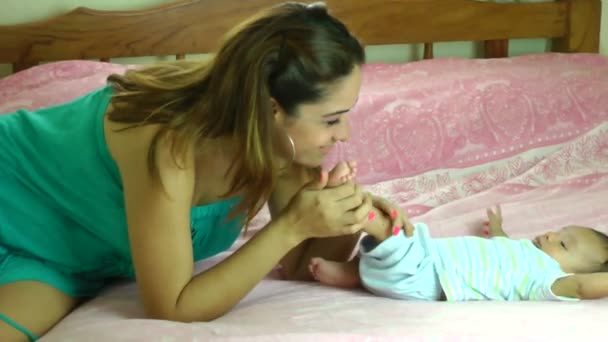 Happy young hispanic mother kissing her two months old sons feet in bed at home