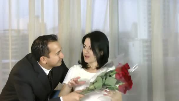 Young happy couple romantic date, celebrating valentine day man give red roses to his wife