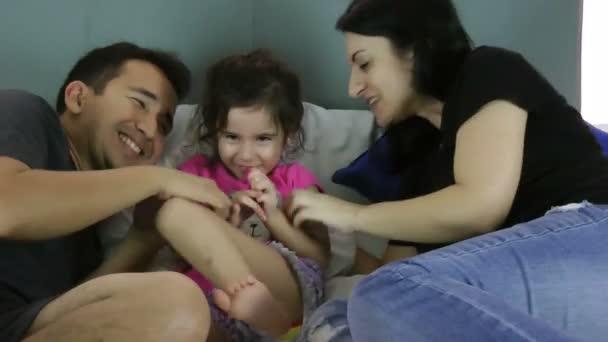 rodiče lechtání své dítě na posteli doma