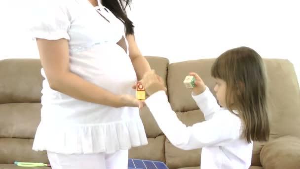 detail břicho těhotné ženy a její dcery drží chlapce kostky