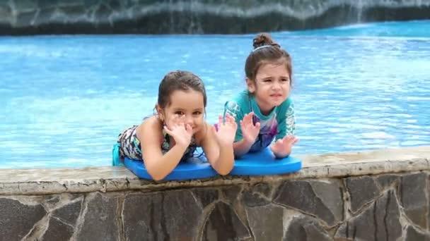 dvě šťastné malé holčičky hrají v bazénu
