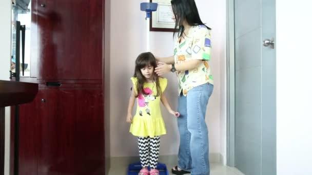 Doktor opatření růst usmívající se dívka v ordinaci