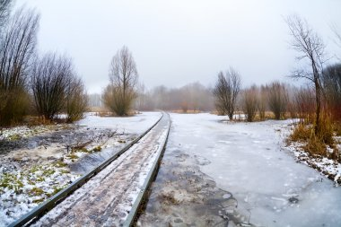 wooden road bridge through frozen lake