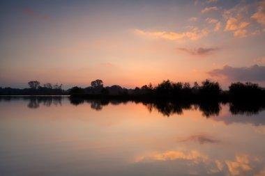 warm gold sunrise over lake