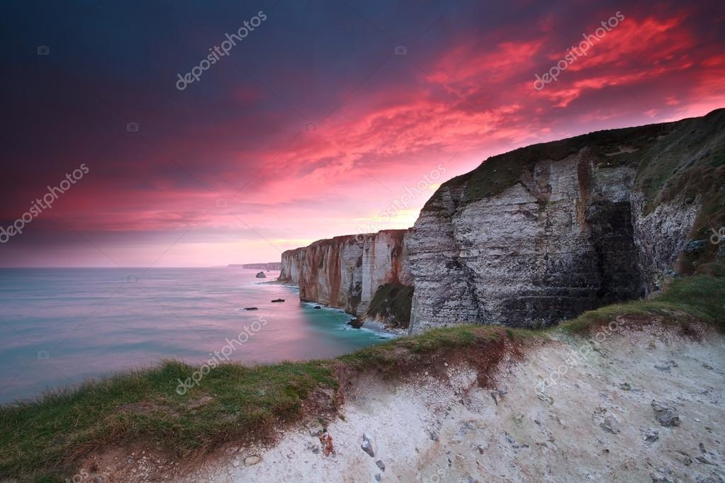 dramatic fire sunrise over cliffs in ocean