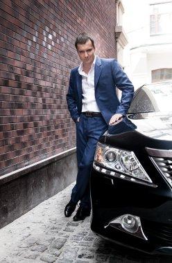 Man in suit posing near car
