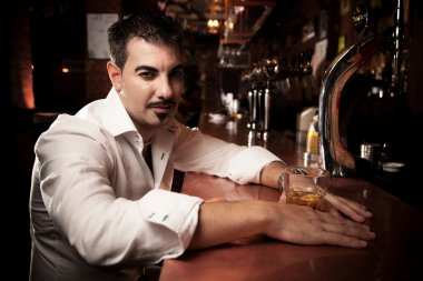 Man in shirt sitting near bar desk