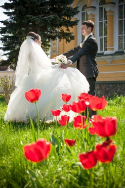 Newly married couple dancing on field with red tulips