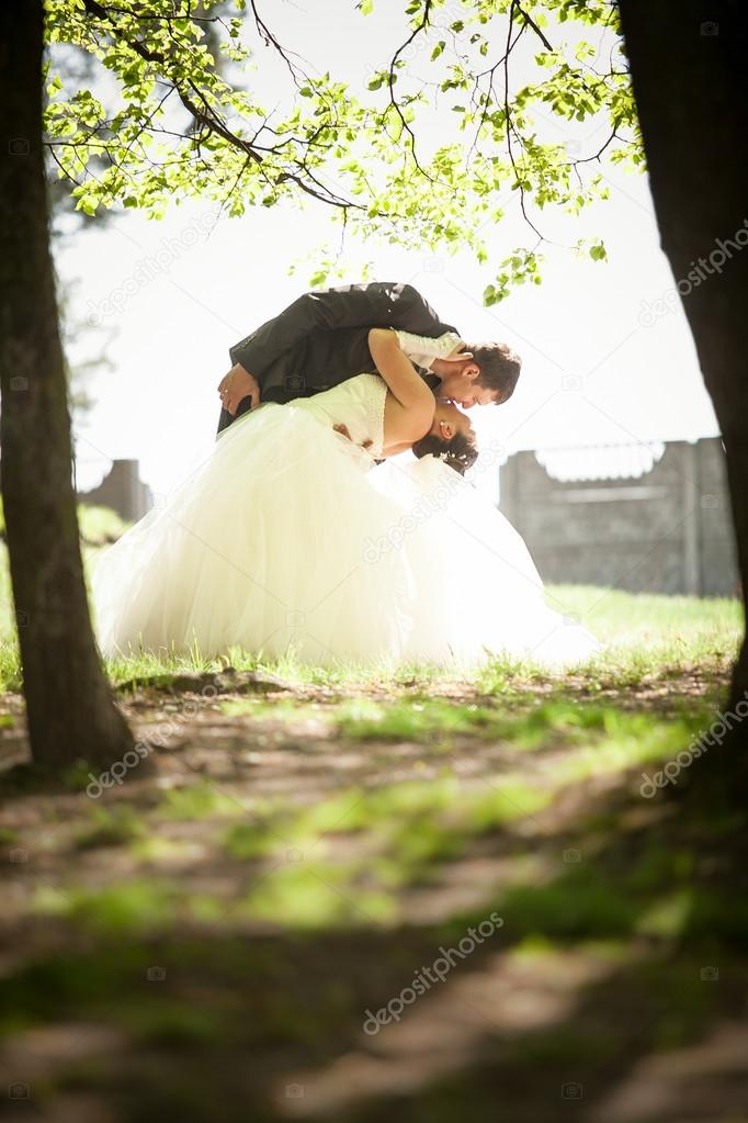married couple dancing and kissing in park