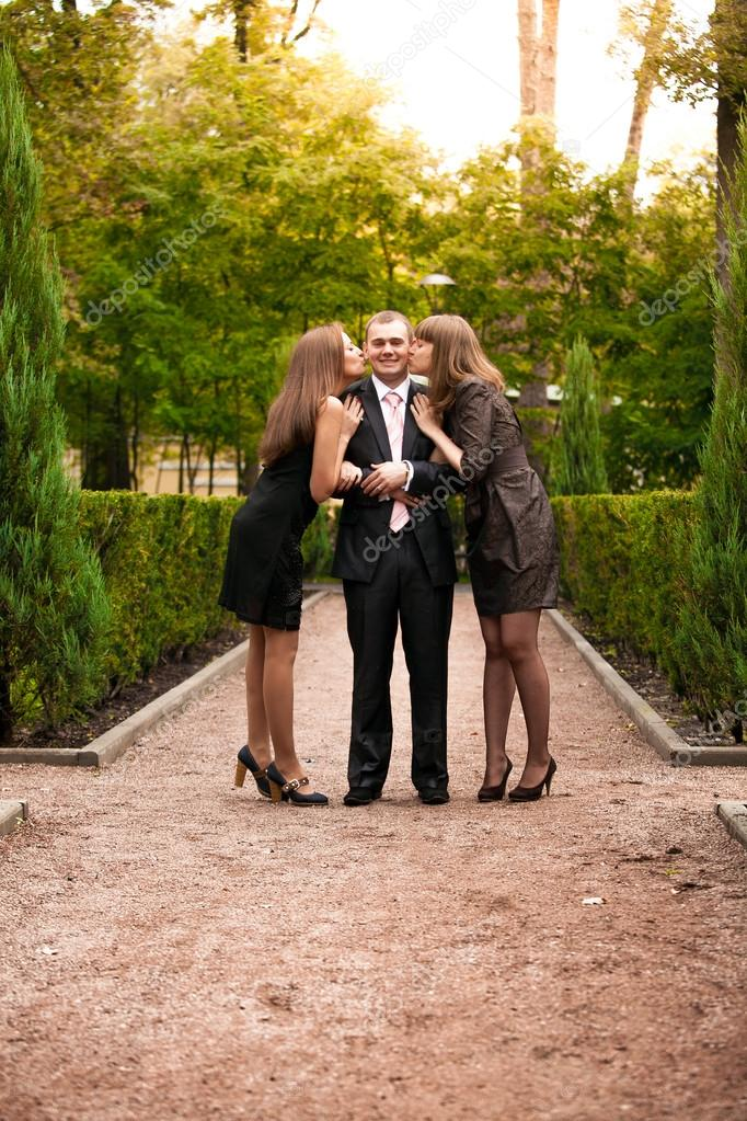 Two girls kissing handsome businessman